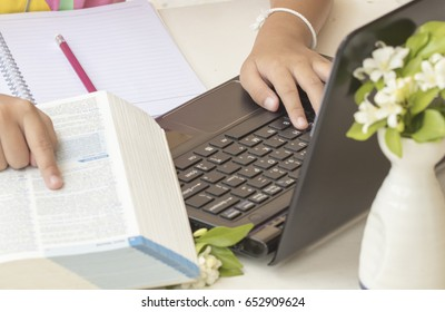 girl writing and reading a book dictionary english for study and computer notebook
