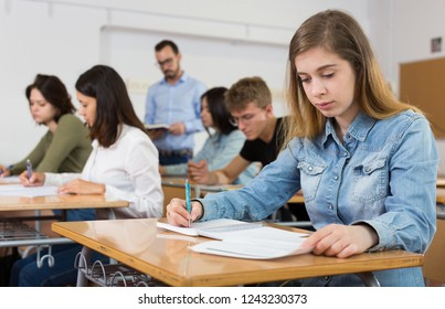 Girl is writing test and answer about task in the classroom.