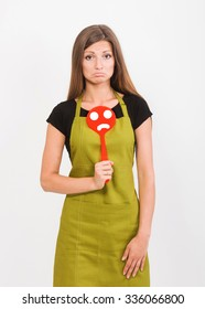 Girl in yellow apron with a sad face spatula