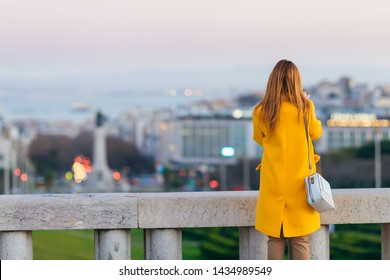 girl in a yellow coat with a handbag near the fence overlooking the city. back view