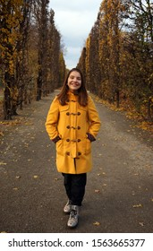 a girl in a yellow coat walks in the park autumn season Augarten Vienna