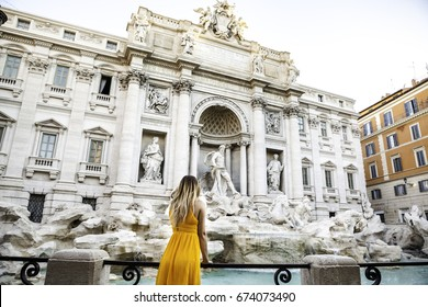 Girl in yellow dress in front of Trevi Fountain, Rome, Italy. Young pretty girl with blonde hair in a yellow dress. Photo shooting in Rome, Italy. Blonde hair. Blonde head