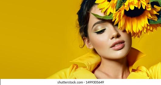 Ein Mädchen in einem gelben Kleid hält in ihren Händen einen Strauß gelber Sonnenblumen.