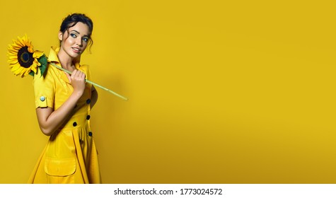 The girl in a yellow dress holds a large sunflower and smiles playfully.