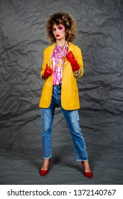 Girl in a yellow jacket and blue jeans with an afro hairstyle. Fashion of the eighties, disco era. Studio photo on gray background.