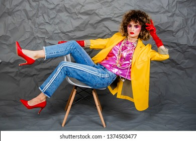A girl in a yellow jacket and blue jeans with an afro hairstyle sits on a chair. Fashion eighties, the era of disco. Studio photo on a gray background.