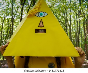 Girl with a yellow pyramid on her head. Absurd funny portrait