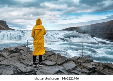 The girl in a yellow raincoat looks at the waterfall Gullfoss in Iceland