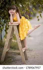 a girl in a yellow sundress on the stairs, girl in a yellow sundress