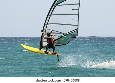 Girl with yellow windsurf jumping.