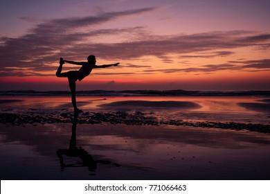 girl yoga at sunset on the beach