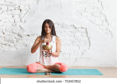 girl  yogi plays on the Tibetan singing bowl. Young woman meditating in a yoga on white background, Yoga and healthy lifestyle concept