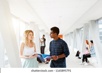 A girl and a young man communicate at the University. The photo illustrates student life, education at University or College.