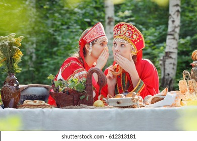 Girl, young russian woman in Russian national sundress, sarafan, and a kokoshnik whispering, emotions, wonder, russian teatime, selective focus