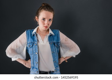 The girl is a young teacher stands akimbo in front of the blackboard