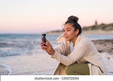 Girl / Young woman at beach vlogging for youtube using the DJI Osmo Pocket gimbal camera. MANDURAH, WESTERN AUSTRALIA. Photographed: March 2019.