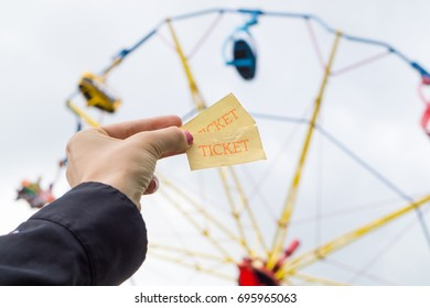 Girl or young woman holding amusement park tickets in hand. Colorful theme park ride in the background.