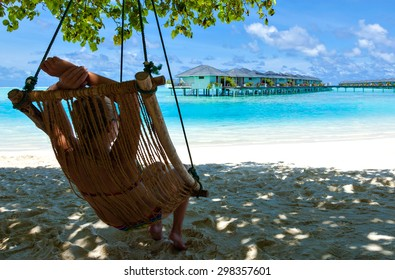 girl young woman lying in a deck chair and looking at a tropical turquoise sea with bungalows on the water on the Caribbean Hawaiian Maldives. Relaxing and enjoying on summer vacation.