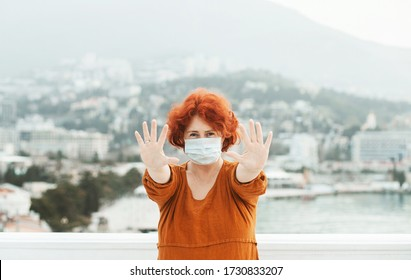 Girl, young woman in protective  medical mask on her face looking at camera outdoors on a fooftop show palm, hand, stop no sign. Coronavirus  pandemic concept.