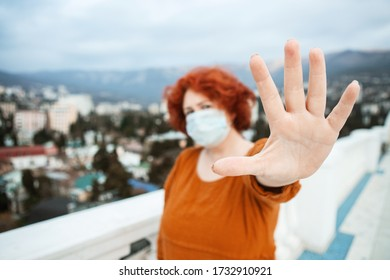 Girl, young woman in protective  medical mask on her face looking at camera outdoors on a fooftop show palm, stop sign. Focus on a hand. Coronavirus  pandemic concept.
