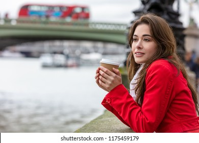 Girl or young woman in a red coat drinking coffee in a disposable cup next to Westminster Bridge with red double decker bus in the background, London, England, Great Britain