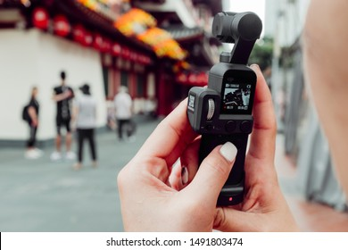 Girl / Young woman vlogging for YouTube using the DJI Osmo Pocket gimbal camera. SINGAPORE, ASIA. Photographed: August 2019.