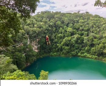 Girl ziplining over the water of a cenote in the Mexican jungle