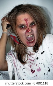 girl of the zombie in anger and fury with a blood-stained knife on a holiday halloween