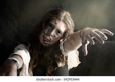 Girl with zombie make-up in a dark background