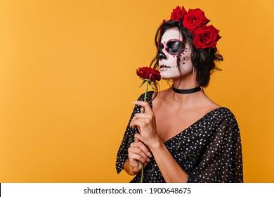 Girl with zombie mask for Halloween smells fragrant rose. Model in black dress on orange background