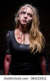 Girl zombie on dark background with blood on her face looking up/Portrait of scary bad zombie woman at night