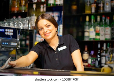 The girl-bartender smiles, wiping the table with a rag at the hotel bar. Brunette bartender in the workplace. Shelves with bottles of alcohol in the background. The concept of work and service.