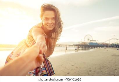Girlfriend inviting his boyfriend to the beach in Santa monica, los angeles