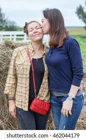 Girlfriend kissing pretty woman on the cheek, countryside