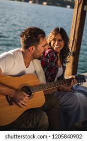 Girlfriend is laughing while boyfriend singing and playing guitar by the river. Beautiful sunset