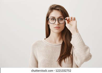 Girlfriend ready to investigate social profile of boyfriend. Portrait of good-looking smart brunette in stylish prescribed glasses looking concentrated at camera, solving issue on char over gray wall