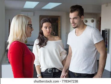 Girlfriend shocked on disloyal boyfriend flirting with woman in red dress, indoors