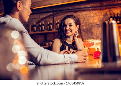 Girlfriend smiling. Beautiful girlfriend smiling while spending time with her loving man in bar