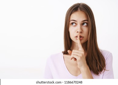 Girlfriend telling secret to friend feeling worried boyfriend find out showing shush gesture while saying shh with index finger over mouth looking at upper left corner worried and intense
