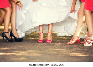 girlfriends of the bride show the bride's feet in red shoes