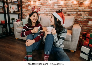 girlfriends chatting on the floor in a warm house. christmas girl with santa hat and deer holding cups and drinking mulled wine. friendship holiday event concept at home.