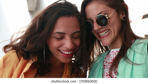 Girlfriends checking cellphone device laughing and smiling