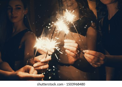 Girlfriends in the darkness holding burning sparklers on holiday
