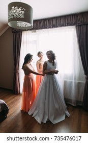 the girlfriends dress the bride for the wedding.