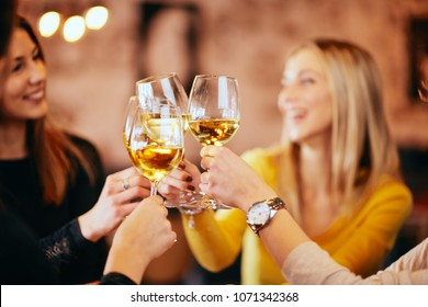 Girlfriends drinking wine and chatting while sitting in the bar.
