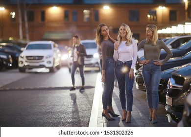 girlfriends evening walk in the city, three girls are walking in the night city near cars and the road, students are walking