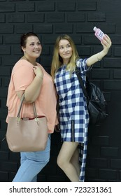 Girlfriends gather for a walk and do selfie before going out. Lovely girl in casual clothes with bags and smartphone.