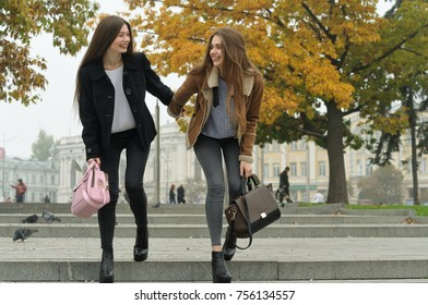 Girlfriends have fun and run down the steps of the sidewalk as they walk down the street. They are fashionable, modern and fun student