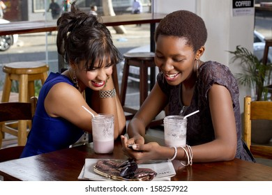 Girlfriends having drink at a coffee shop playing on a phone