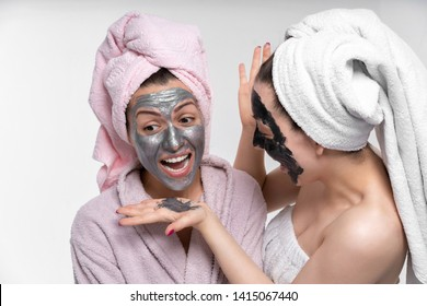 girlfriends help each other put on face a cosmetic mask, having fun and indulge in the process. Girls care about each other and have a great time.